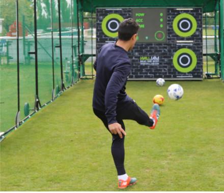 A man kicking a football at a target